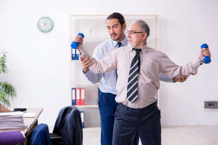 Two employees doing physical exercises at workplace