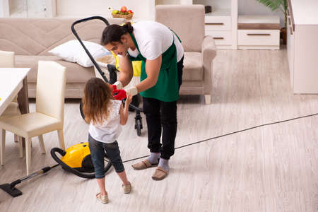 Young male contractor cleaning the house with his small daughter Фото со стока