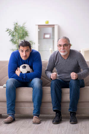 Father and son watching soccer on tv Stockfoto