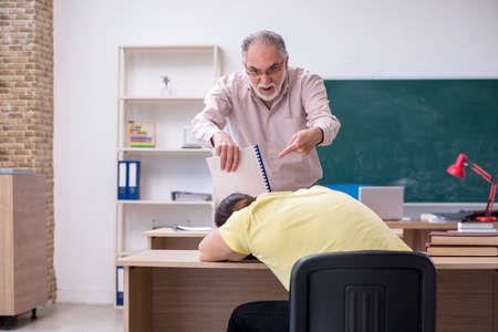 Old teacher and young male student in the classroom Stockfoto