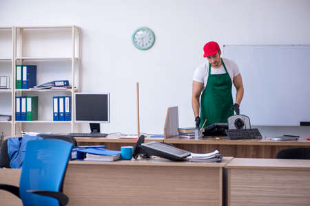Young male contractor cleaning the office Фото со стока
