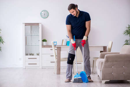 Young leg injured contractor cleaning the house Фото со стока
