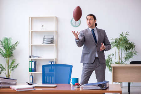 Young male employee with rugby ball in the office Foto de archivo