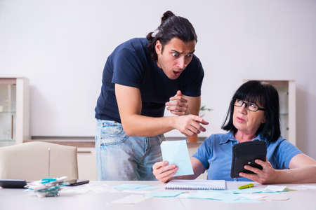 Female pensioner and her young son in budget planning concept