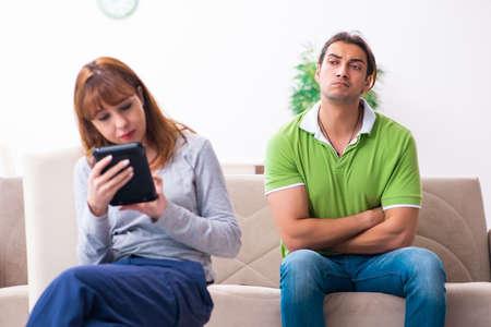 Young couple in gadget dependency concept Foto de archivo