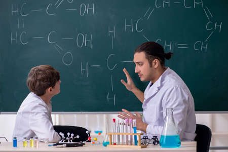 Young chemistry teacher and schoolboy in the classroom