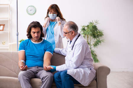Two doctors visiting sick young man at home