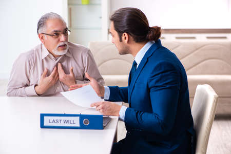 Young male lawyer visiting old man in testament concept