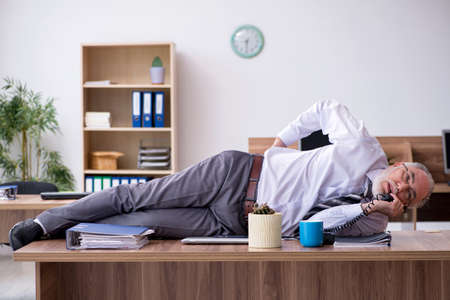 Old male employee suffering from radiculitis at workplace