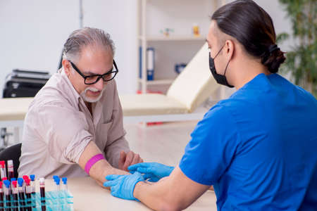 Old patient visiting young male doctor in blood transfusion Stok Fotoğraf