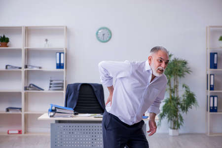 Aged male employee doing physical exercises during break Stockfoto
