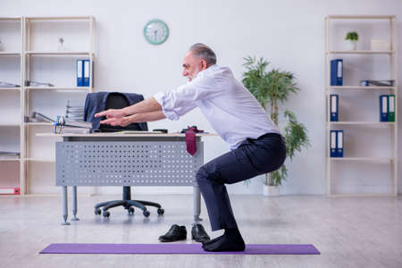 Aged male employee doing physical exercises during break