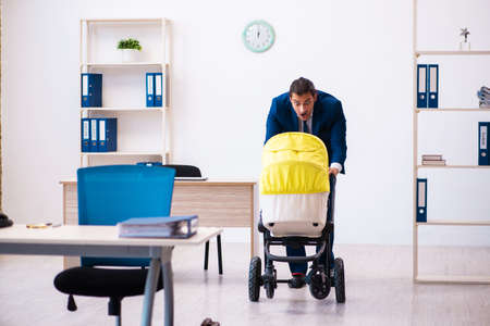 Young male employee looking after kid at workplace Stock fotó