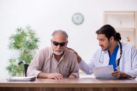 Old blind man visiting young male doctor Stock Photo