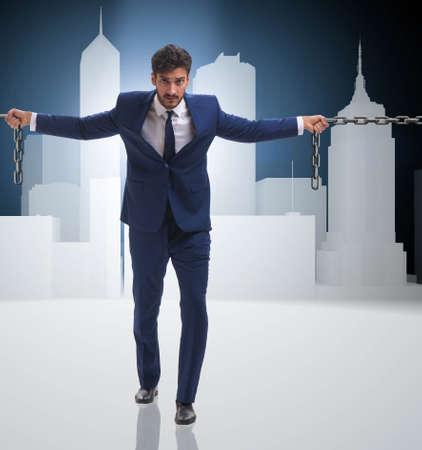 Businessman holding chains in business concept Foto de archivo