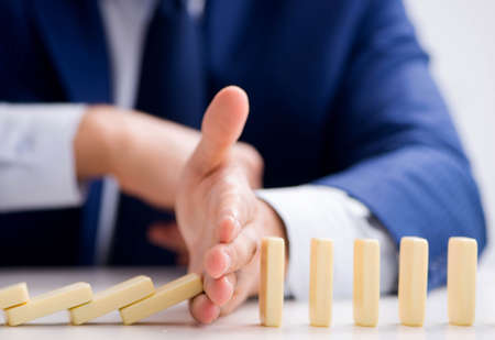 Young businessman playing with domino in office Stock Photo