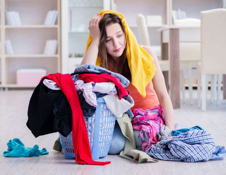 Stressed woman doing laundry at home Foto de archivo