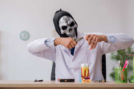 Devil doctor stomatologist working in the clinic Banco de Imagens