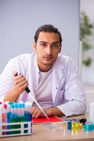 Young male chemistry teacher in the classroom
