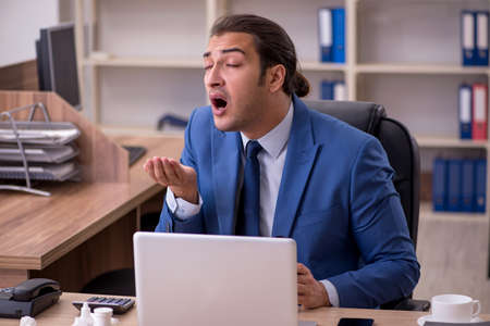 Young sick businessman employee suffering at workplace
