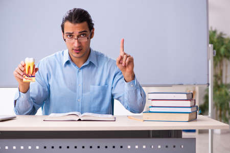 Young male teacher dentist in front of whiteboard