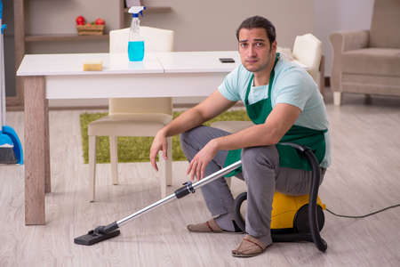 Young male contractor cleaning the house Stockfoto