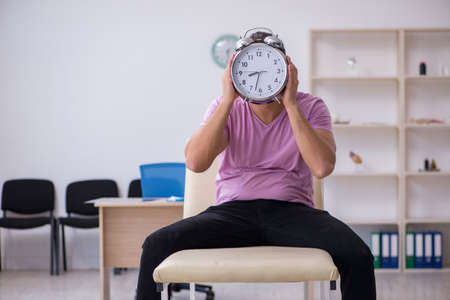 Young male patient waiting for doctor in time management concept