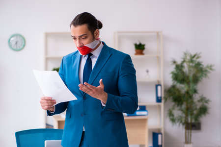 Mouth closed male employee working in the office Stockfoto