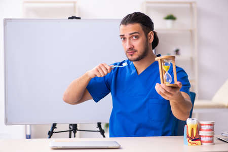 Young male doctor teacher dentist in front of whiteboard
