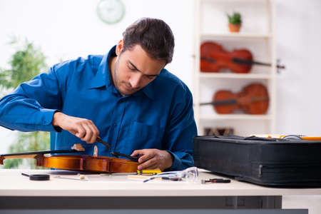 Young male repairman repairing violin