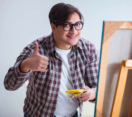 Young male artist drawing pictures in bright studio Standard-Bild