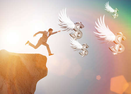 Businessman chasing angel dollars in business concept
