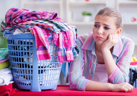 Tired depressed housewife doing laundry Stockfoto