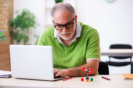 Old male student physicist studying molecular model