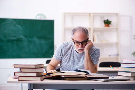 Old male student preparing for exams in the classroom