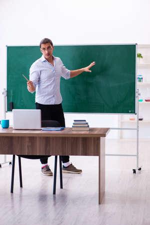 Young male teacher in front of blackboard 版權商用圖片