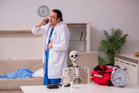 Young male paramedic visiting skeleton patient 版權商用圖片