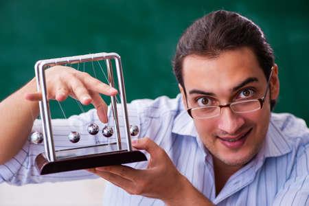 Young male teacher physicist in front of blackboard 版權商用圖片