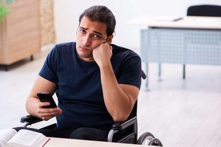 Young male student in wheel-chair preparing for exams