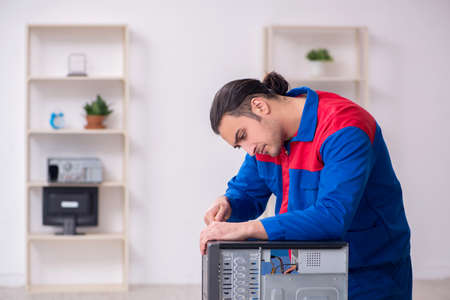 Young male repairman repairing computer