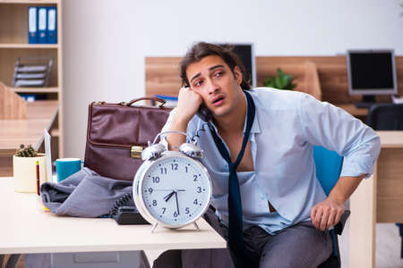 Young male employee being late for his job