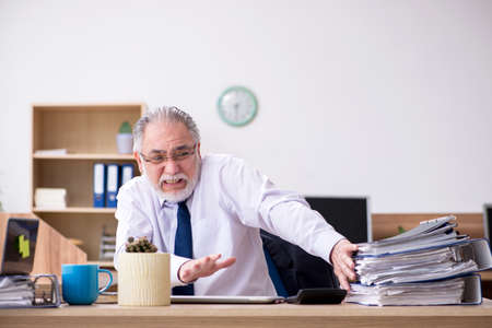 Old male employee working in the office