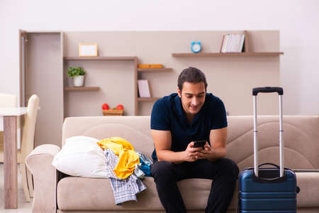 Young man preparing for journey at home