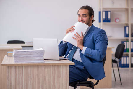 Young male employee and too much work in the office