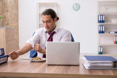 Hungry male employee eating buckwheat during break