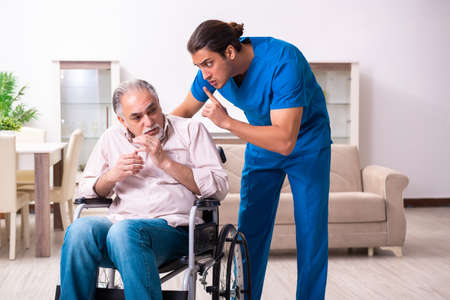 Old man in wheel-chair and young bad caregiver indoors Imagens