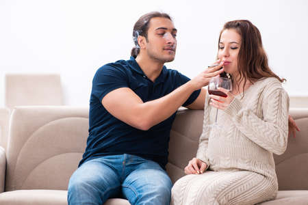 Man and pregnant woman in harmful habits concept