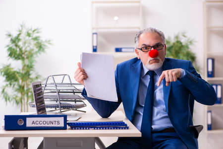 Old businessman clown working in the office