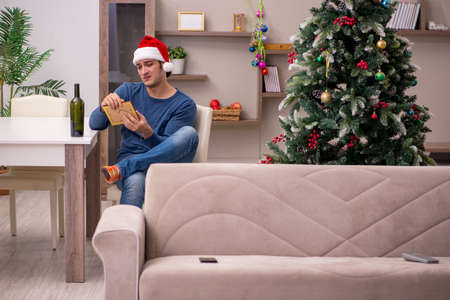 Young man celebrating Christmas alone at home