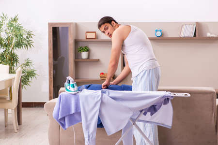 Young male employee ironing in the morning Stock Photo